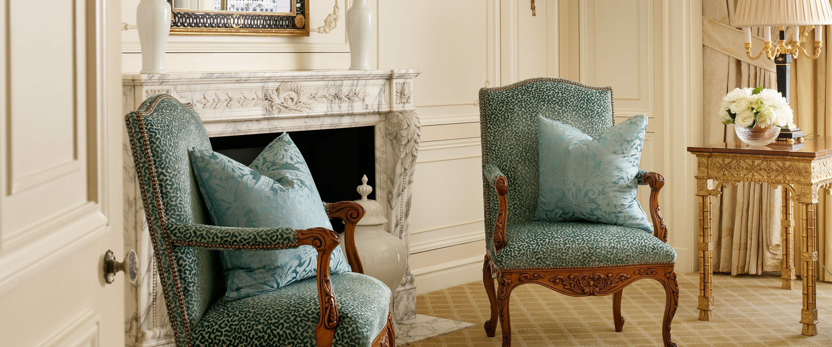 Two luxury lounge chairs by the fireplace at the Westgate Room restaurant.