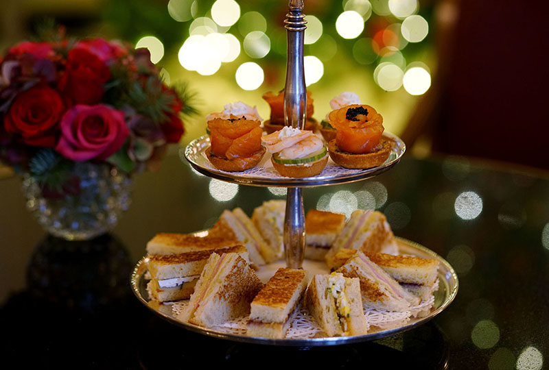 Christmas Tea sandwiches with holiday lights in background.